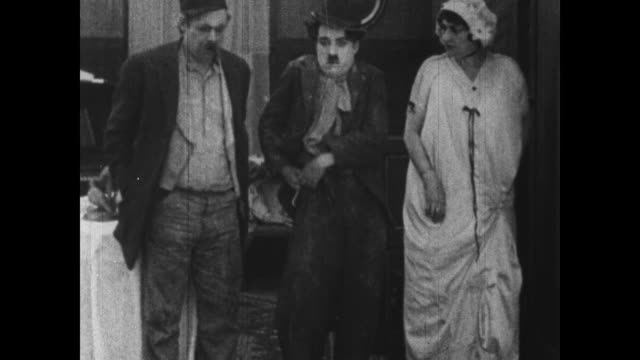 1915 Suspicious woman locks silver in safe in front of worker Charlie Chaplin and his boss who in turn to hide their watches