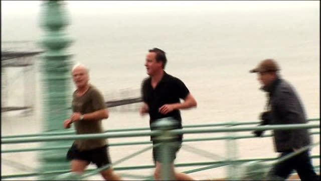 brighton: ext david cameron mp jogging along seafront as runs into building entrance - 黒のシャツ点の映像素材/bロール