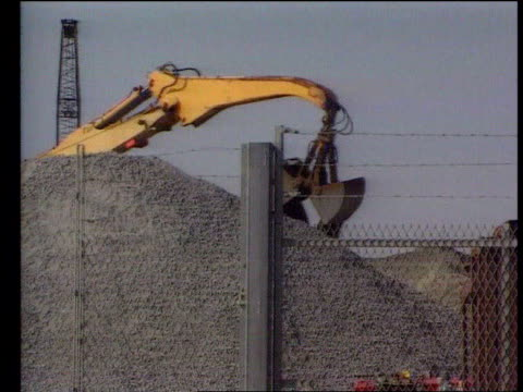 shoreham lms cargo vessel at dockside as crane at work unloading aggregate lms crane dropping scoop load of aggregate onto pile on dockside track... - ショーハム・バイ・シー点の映像素材/bロール