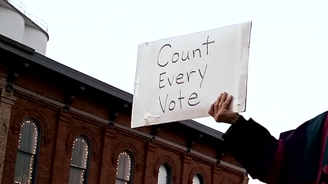 suzy morse holds up a simple count every vote sign to passing motorists in the business district of a small michigan town. the trump campaign has... - fraud stock videos & royalty-free footage