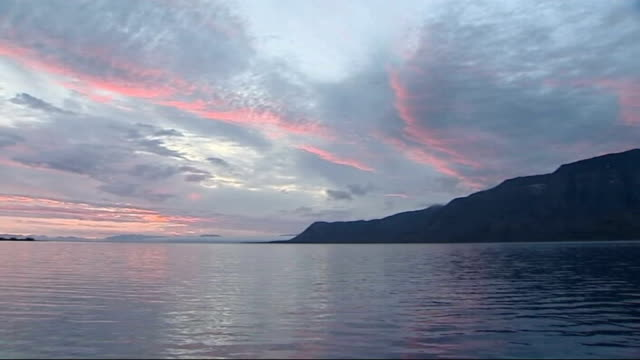 svalbard ext / dusk good shots of arctic ocean pink light reflecting on water's surface land in distance - svalbard and jan mayen stock videos & royalty-free footage