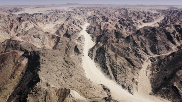 vídeos de stock, filmes e b-roll de swakopmund lua paisagem namíbia vídeo aéreo moonscape canyon road - namíbia