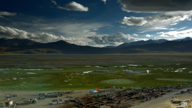 Swampy land in an arid landscape with a deserted nomad village in the foreground