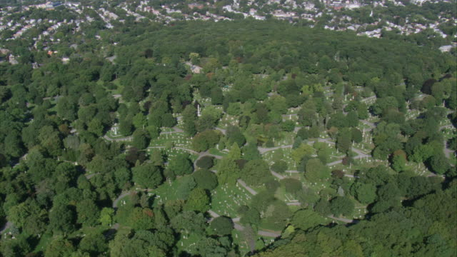 AERIAL Swan Point Cemetery with distant view of burial markers nestled among the trees / Providence, Rhode Island, United States