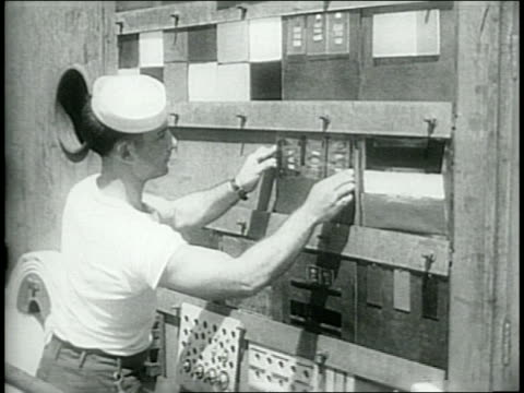 swancutt and wood inspect final preparations for their flight / target ships assembled in bikini atoll / sailor mounts test materials to side of ship... - bikini atoll stock videos & royalty-free footage