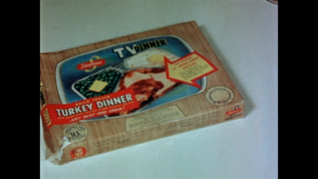 cu of swanson turkey tv dinner box depicting the food inside / inner foil tray on top of outer box / female hand removes foil topping to reveal the... - advertisement stock videos & royalty-free footage