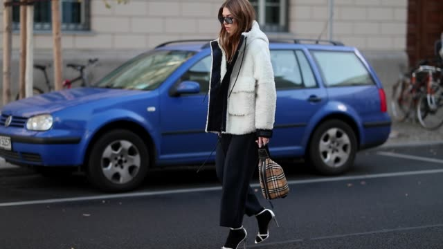 Swantje Soemmer is seen wearing white teddy jacket Sportmax black pants Sportmax Burberry belt bag Steve Madden heels in socks Orgreen sunglasses on...