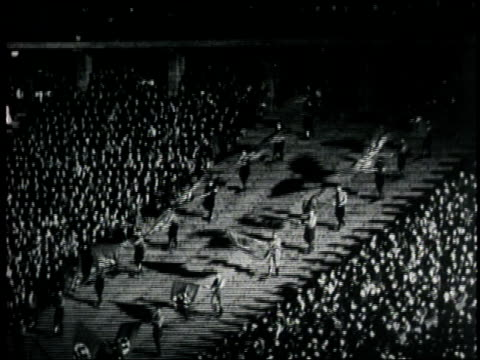 a swastika banner hangs over nazi soldiers who wave flags during a ceremony - hakenkreuz stock-videos und b-roll-filmmaterial