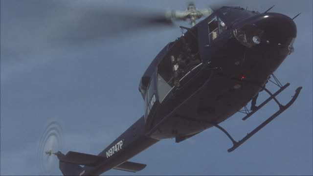 A swat team jumps out of a black police helicopter.