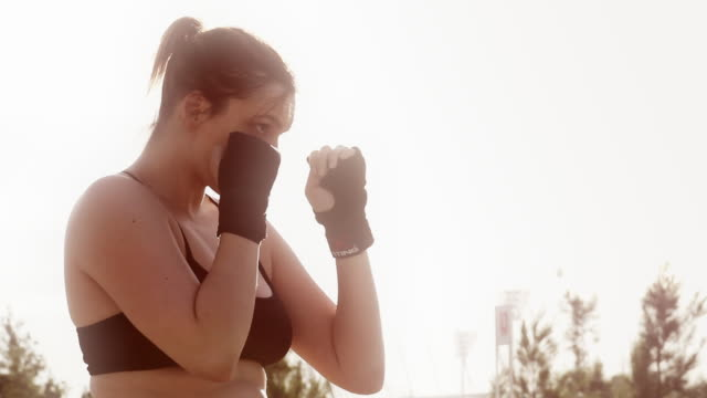 sweat drenched woman in a boxing stance - genderblend stock videos & royalty-free footage