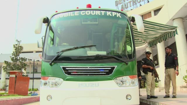 sweat pours down judge fazal wadood's back as he sits perched behind a desk inside a custombuilt green bus that is the latest weapon in the battle... - peshawar video stock e b–roll