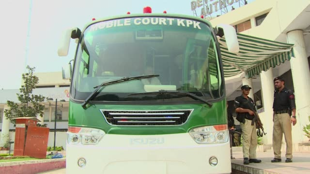 sweat pours down judge fazal wadood's back as he sits perched behind a desk inside a custom-built green bus that is the latest weapon in the battle... - peshawar stock videos & royalty-free footage