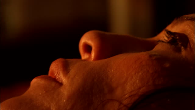 sweat trickles down the face of a woman with a fever. - 生理学点の映像素材/bロール