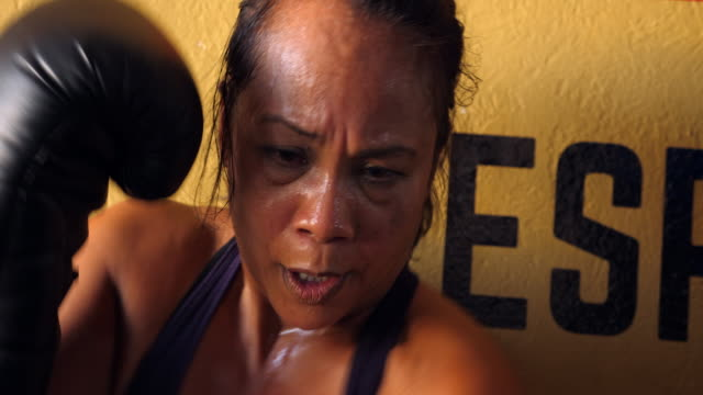 cu sweating female boxer working out in boxing gym - sportswear stock videos & royalty-free footage
