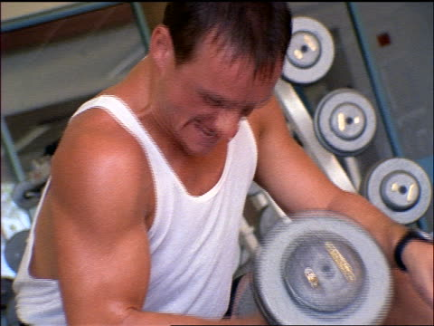 canted sweating man doing bicep curls with dumbbell in gym - ハンドウェイト点の映像素材/bロール