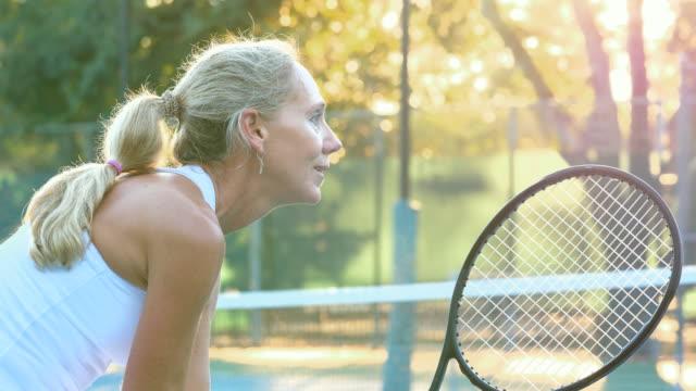 stockvideo's en b-roll-footage met ms sweating mature female tennis player waiting for return at net during tennis match - paardenstaart haar naar achteren