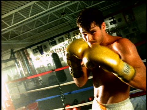 Sweaty boxer shadow boxing camera in gym