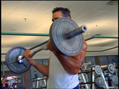 sweaty man doing biceps curls with barbell in gym / nyc - arm curl stock videos and b-roll footage
