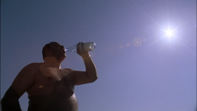 A sweaty man drinks from his water bottle under the hot sun.