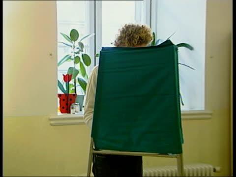 sweden votes against joining euro; itn sweden stockholm int man holding baby as along to vote in polling station woman marking slip behind screen two... - röstsedel bildbanksvideor och videomaterial från bakom kulisserna