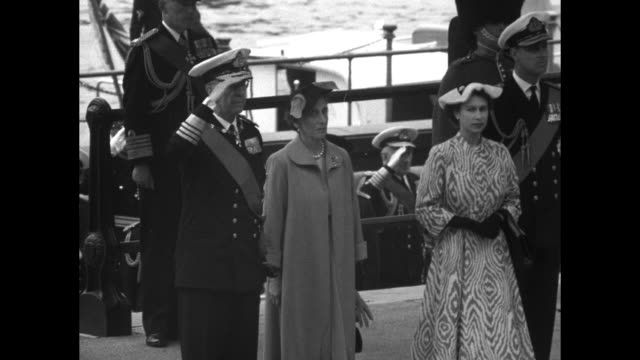 Sweden's King Gustaf VI Adolf and Queen Louise stand on deck of launch with Queen Elizabeth II and Prince Philip Duke of Edinburgh King salutes / WS...
