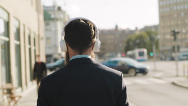 a swedish businessman is walking down the street listening to music - rear view stock videos & royalty-free footage