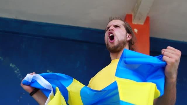 schwedischer fan ein fußballspiel ansehen - schweden stock-videos und b-roll-filmmaterial