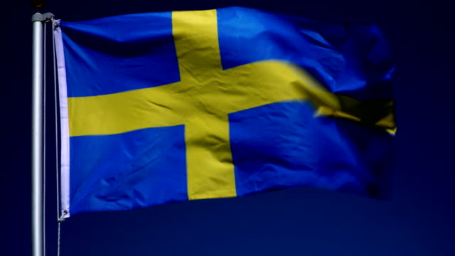 4K: Swedish Flag on Flagpole in front of Blue Sky outdoors (Sweden)