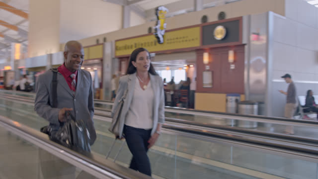 stockvideo's en b-roll-footage met sweep past diverse businessman and woman as they walk down moving sidewalk in airport terminal. - voetgangerspad