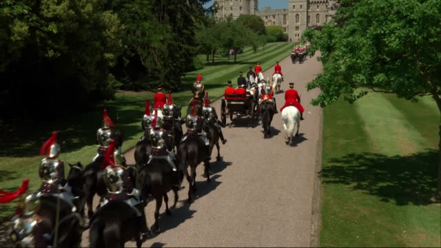 Sweeping crane shot showing the newlywed Duke and Duchess of Sussex approaching the George IV Gateway by horsedrawn carriage