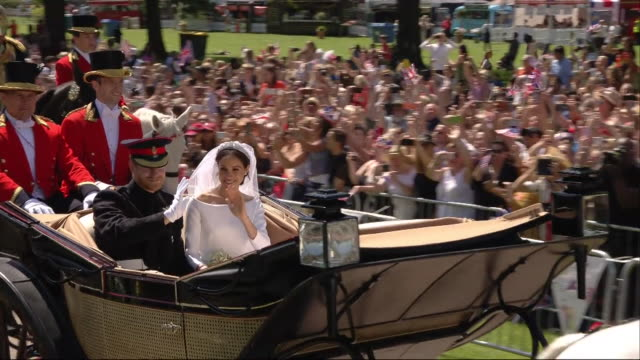 Sweeping crane shot showing the newlywed Duke and Duchess of Sussex passing scores of wellwishers in a horsedrawn carriage