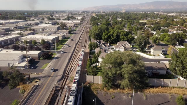 a sweeping drone clip looking down on a commuter train in salt lake city - commuter train stock videos & royalty-free footage