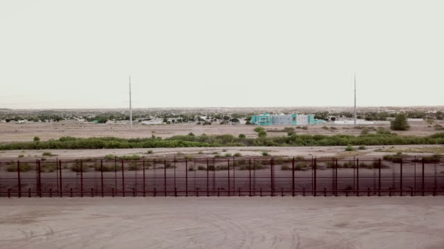 sweeping drone clip of the international border wall near socorro, texas and ciudad juarez, mexico - international border stock videos and b-roll footage