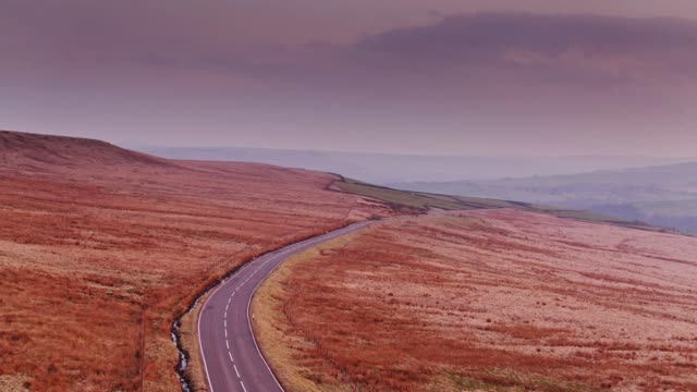 sweeping drone flight over winding country road between oxenhope and hebden bridge, england - pennines stock videos and b-roll footage