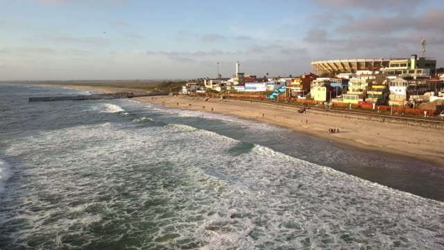 sweeping drone point of view of the beach and boardwalk near the international border wall in playas tijuana, mexico - international landmark video stock e b–roll