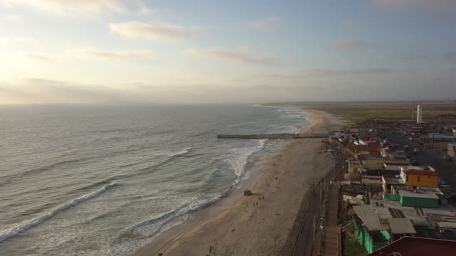 sweeping drone point of view of the beach and boardwalk near the international border wall in playas tijuana, mexico - united states border patrol stock videos & royalty-free footage
