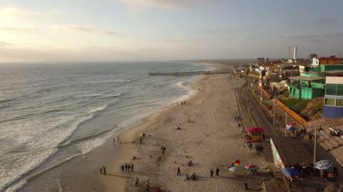 プラヤスティファナ、メキシコの国際境界壁の近くのビーチと遊歩道の無人ドローンポイント - バハカリフォルニア点の映像素材/bロール