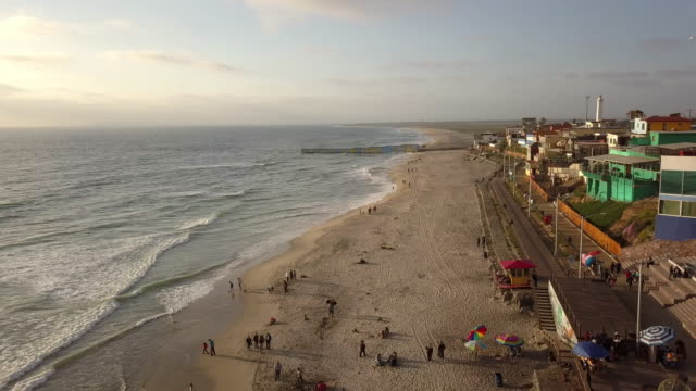 vídeos de stock e filmes b-roll de sweeping drone point of view of the beach and boardwalk near the international border wall in playas tijuana, mexico - península de baixa califórnia