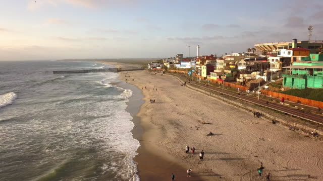 sweeping drone point of view of the beach and boardwalk near the international border wall in playas tijuana, mexico - international border stock videos and b-roll footage