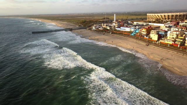 sweeping drone point of view of the beach and boardwalk near the international border wall in playas tijuana, mexico - international border stock videos & royalty-free footage