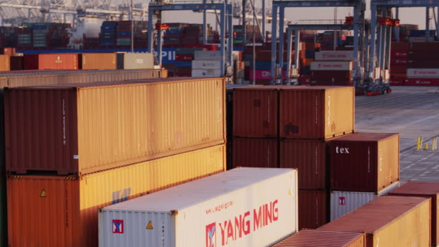 sweeping drone shot around cargo containers in shipping terminal - box container stock videos and b-roll footage