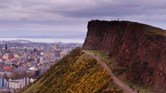 sweeping drone shot around salisbury crags, edinburgh - scottish culture video stock e b–roll