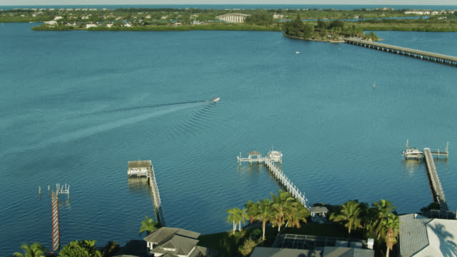 sweeping drone shot of houses with boat docks in vero beach and the wabasso causeway bridge - lagoon stock videos & royalty-free footage