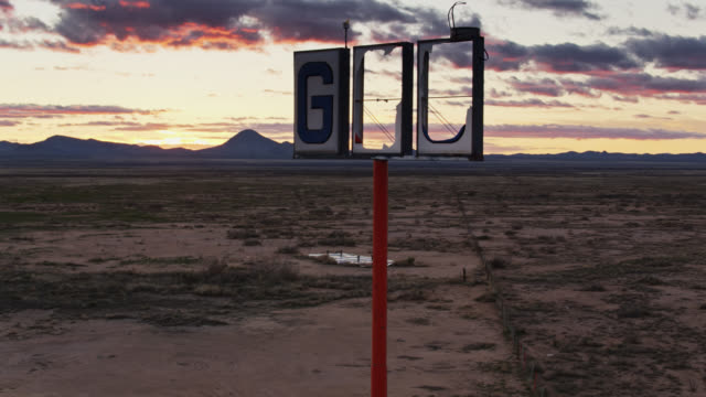 sweeping drone shot revealing i-10 through holes in broken gas station sign - interstate 10 stock videos & royalty-free footage