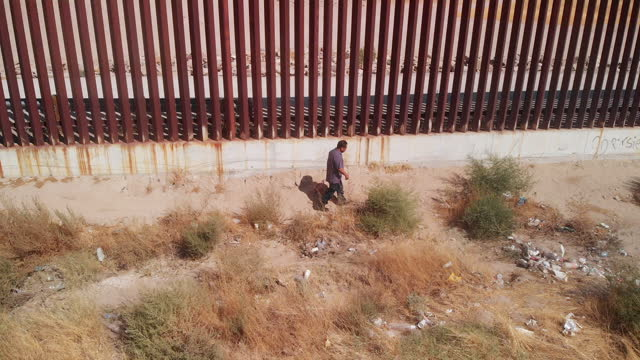 a sweeping drone view of a mexican man walking along the united states and mexico international border wall between sunland park new mexico and puerto anapra, chihuahua mexico - international border stock videos & royalty-free footage