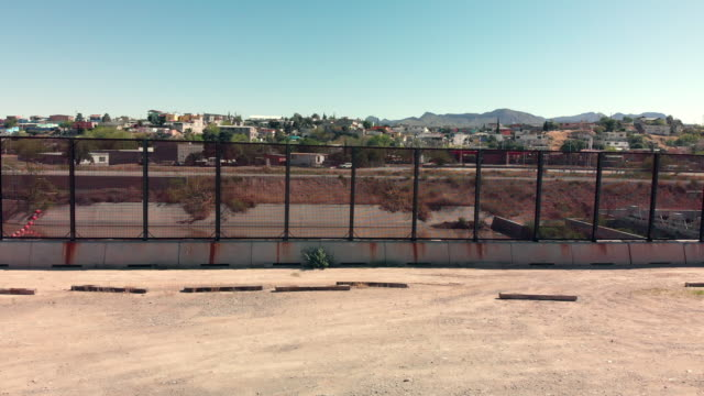 a sweeping drone view of the border wall dividing el paso, texas, usa and ciudad juarez, mexico - international border stock videos & royalty-free footage