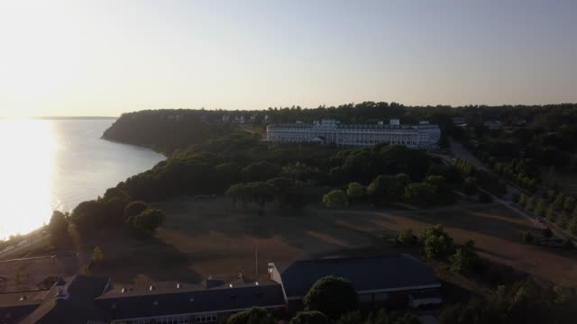 a sweeping drone view of the cozy little town of mackinac on mackinac island at sunset - lake michigan stock videos & royalty-free footage