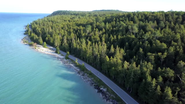 a sweeping drone view of the cozy little town of mackinac on mackinac island - lake michigan stock videos & royalty-free footage