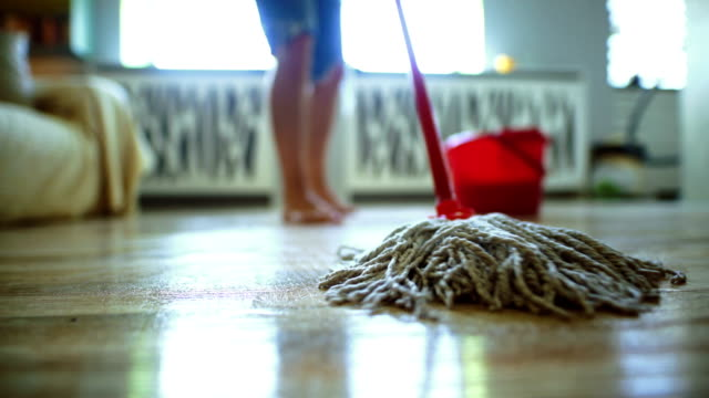 Sweeping the floor with a mop.