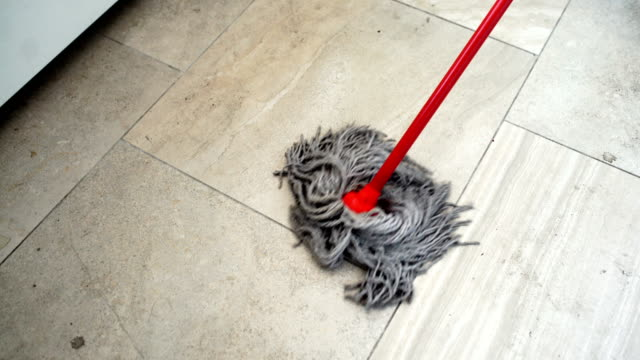 sweeping the floor with a mop. - pavimento video stock e b–roll